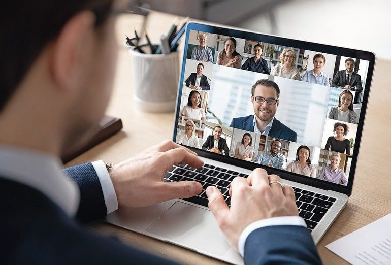 Rear_view_of_businessman_speak_on_web_conference_with_diverse_colleagues_using_laptop_Webcam,_male_employee_talk_on_video_call_with_multiracial_coworkers_have_online_meeting_briefing_from_home