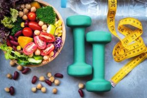 Fresh_vegetable_salad_and_healthy_food_for_sport_equipment_for_women_diet_slimming_with_measure_tap_for_weight_loss_on_wood_background._Healthy_Sport_Concept_