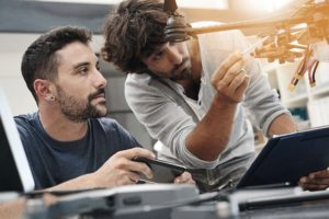 Engineer_and_technician_working_together_on_drone_in_office
