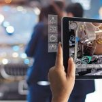 Augmented_reality_concept._AR._Industrial_4.0_,_Hand_of_engineer_holding_tablet_using_virtual_AR_service_application_to_check_the_work_of_electric_machine_on_car_showroom_background