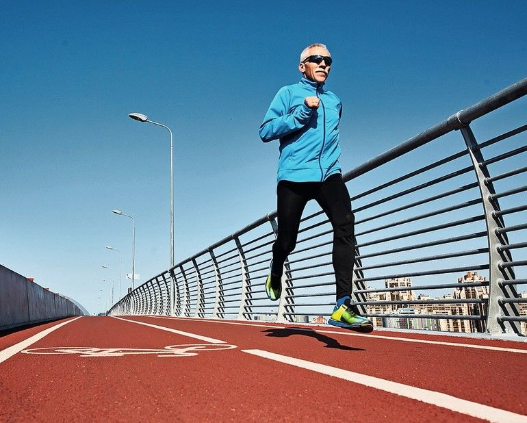 Low_angle_view_of_concentrated_senior_sportsman_jogging_outdoors_and_enjoying_sunny_warm_day,_full_length_portrait