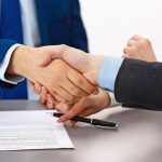Business_people_shaking_hands,_finishing_up_a_papers_signing._Meeting,_contract_and_lawyer_consulting_concept.