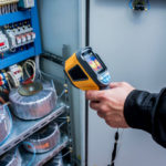 Technician_use_infrared_thermal_imaging_camera_to_check_temperature_at_fuse-box._Modern_equipment