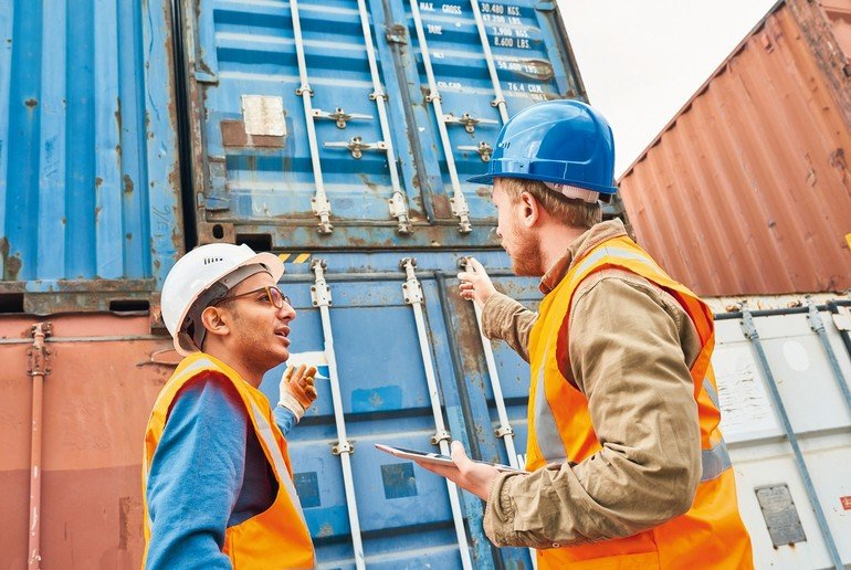 Two_confident_supervisors_wearing_reflective_vests_and_hardhats_discussing_details_of____loading_ship_with_container_storage_units_while_gathered_together_in_port