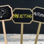 Concept_message_MARKETING_AUTOMATION_and_light_bulb_as_symbol_for_idea_written_with_chalk_on_wooden_mini_blackboard_labels,_defocused_chalkboard_and_wood_table_in_background