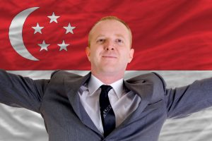joyful_investor_spreading_arms_after_good_business_investment_in_singapore,_in_front_of_flag