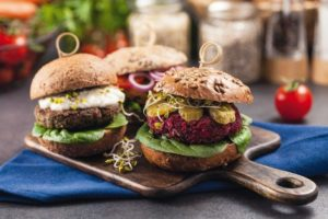 Vege_burgers_with_carrots,_beetroots_and_mushrooms._Front_view._Black_background.